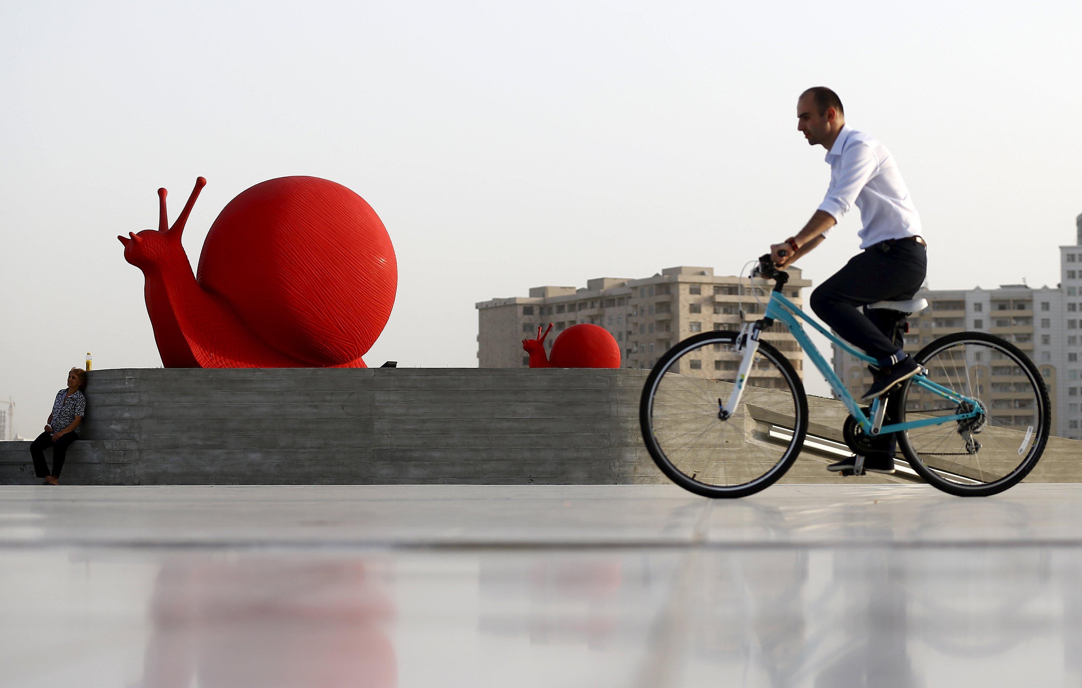 Seorang pria bersepeda melewati instalasi di depan Heydar Aliyev Center di Baku, Azerbaijan, Senin (15/6). ANTARA FOTO/REUTERS/Stoyan Nenov.