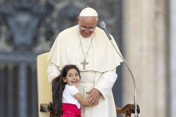 Seorang anak tersenyum ketika memeluk Paus Fransiskus saat memimpin misa bagi peserta Konvensi Keuskupan Roma di lapangan Santo Peter di Kota Vatikan, Minggu (14/6). ANTARA FOTO/REUTERS/Giampiero Sposito.